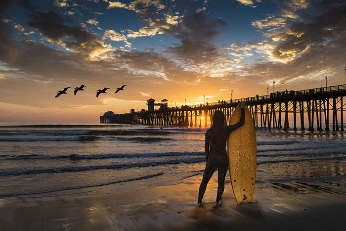long hair surfer standing with surfboard at Oceanside Beach with Oceanside Pier at sunset